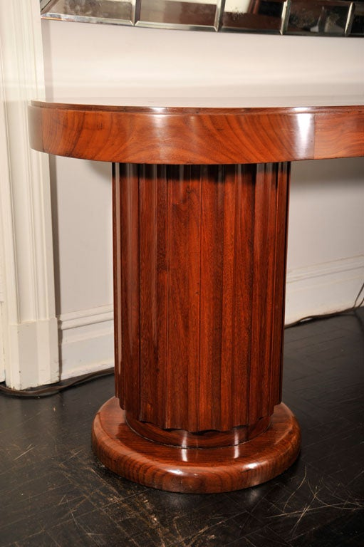 Early 20th century mahogany oval centre table. Pair of columnar fluted pedestals on circular bases, polished top.