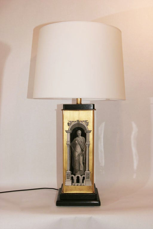 A pair of 1950s architectural form table lamps, attributed to designer Piero Fornasetti, decorated and gold leafed on the reverse side of two glass forms, with black lacquered  mounts. Shades not included