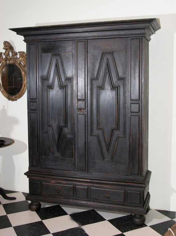 A Swedish Baroque black painted cabinet with two doors and a large drawer.
