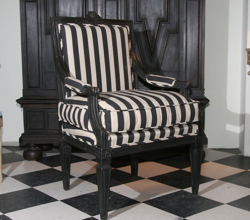 Armchair Swedish Gustavian 19th century Sweden. An armchair made during the Gustavian period 1790-1810. Black painted with carvings, tapered and reeded legs and . Upholstered in a black and white striped cotton fabric. Seat with a loose cushion.