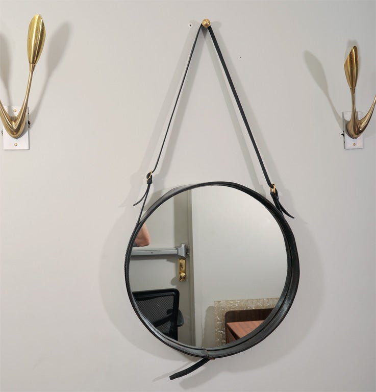 Elegant pair of Jacques Adnet mirrors with a belt. In the rare 18