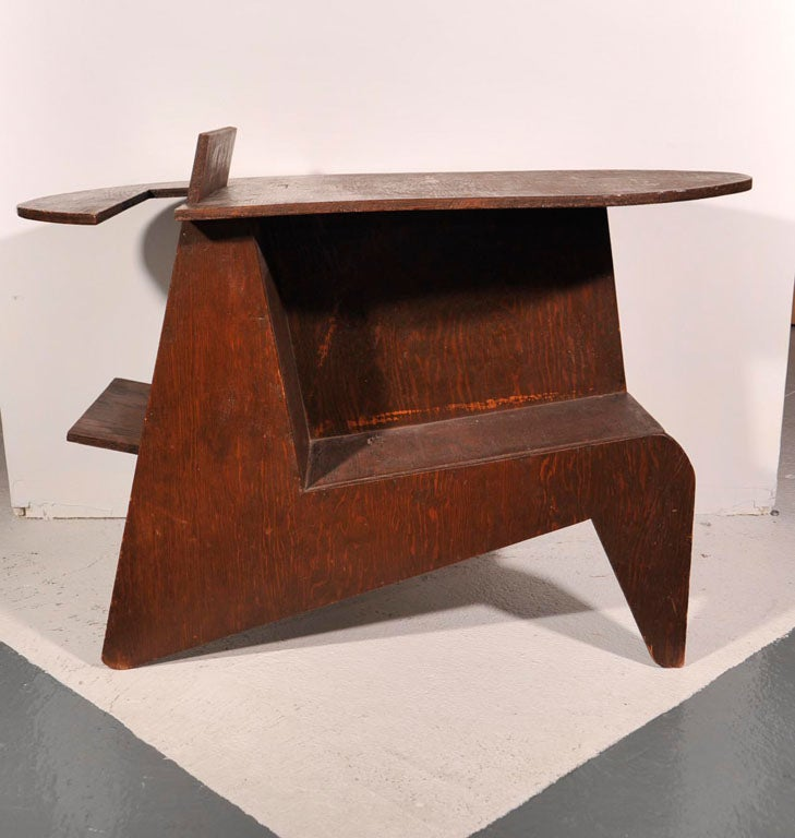 Organic design endtable/nightstand in stained oak with palette shaped top and storage areas for books and magazines and interesting confluence of shapes.