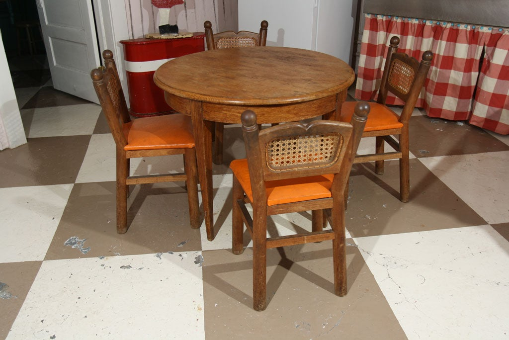 Small round oak table with four cane back cottage chairs. Found in Paris.