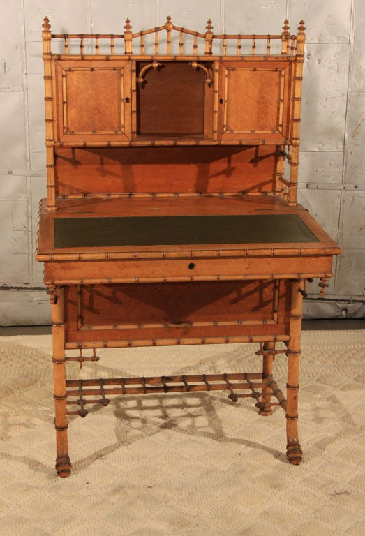 Fantastic late 19th century bird's eye maple secretary desk with faux bamboo details and lift top green leather writing surface.