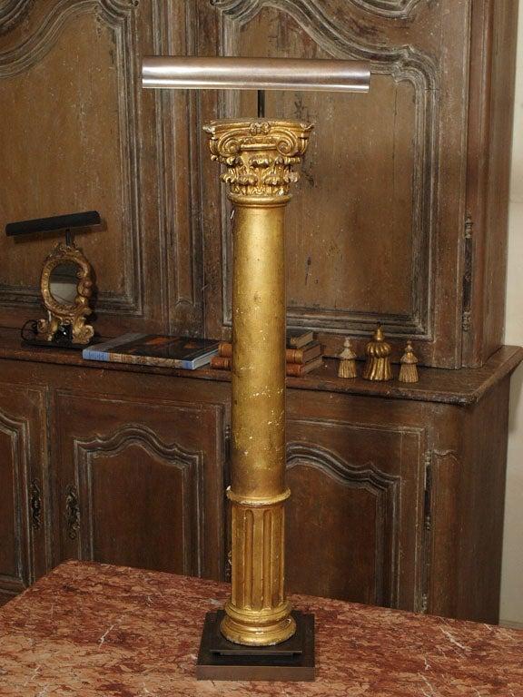 Pair of gilded wood columns (probably decorative furniture elements) made into lamps set on steel bases, illuminated with adjustable picture lights