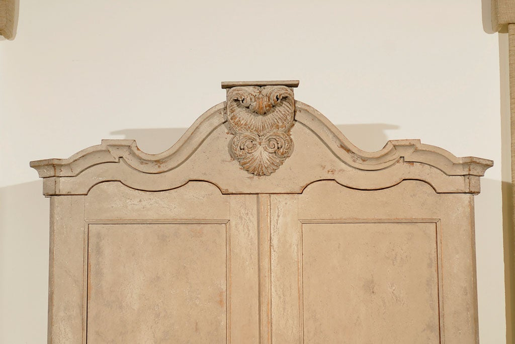 A Dutch Rococo painted linen press from the late 18th century, with carved crest, two doors and bombé chest. Created in the Netherlands during the last decade of the 18th century, this tall cabinet features a bonnet type cornice, accented with an