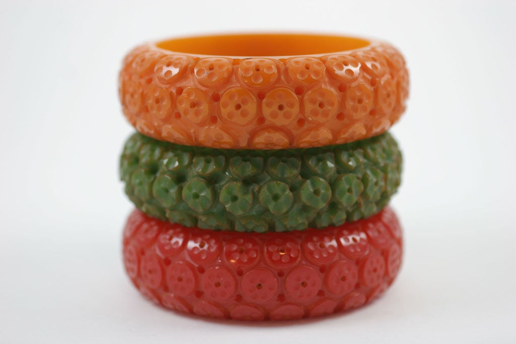 "Set of three Bakelite bangle bracelets in green, red and mustard. Carved with linear lobed concentric circles.  Nicknamed ""Sucker"" bracelets, because the carved motifs resemble the suction cups of octupi.  See same design in ""The Bakelite"