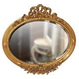 Antique French gold leaf oval beveled mirror.