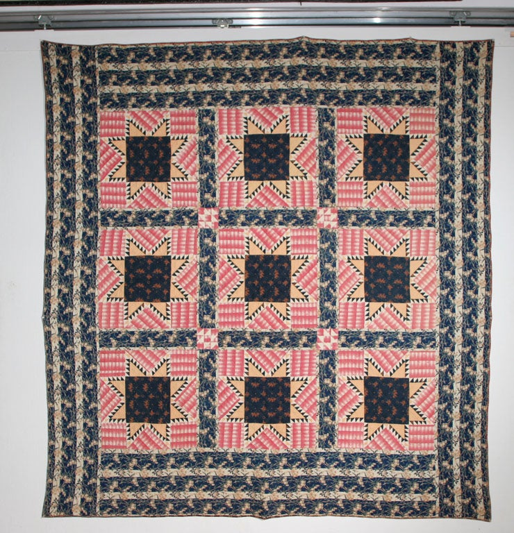 Unusual graphic rendition of traditional pattern in rare period fabrics.  Border is a striped floral print with exceptional colors of indigo and green.  Backing is an extraordinary coppery seaweed print.  Fabrics in the quilt were most likely