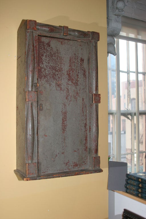Early architectural Federal wood wall cupboard with applied carved wood in gray over red paint.  Two inner shelves, original key and lock. New England.  Circa 1820 - 1840.