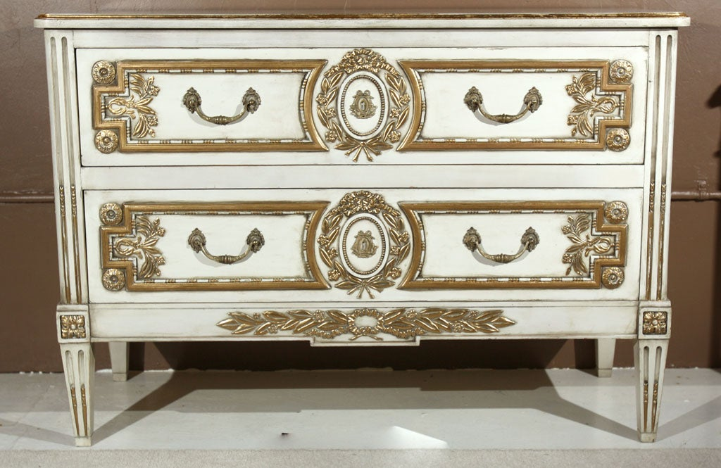 A very unique two-drawer commode, circa 1940s, thoroughly creme peinte and parcel gilded, the rectangular beveled top over a conforming case of two drawers, elegantly carved medallion, wreath, and floral patera decorated with ormolu and gilded