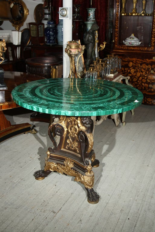 A SOLID  BRONZE  TABLE BASE, PATINATED AND GILDED, FEATURING GROTESQUE ANIMAL MASKS, PAW FEET, SCROLLS AND DECORATIVE ELEMENTS, TRIFOIL  FORM. <br />