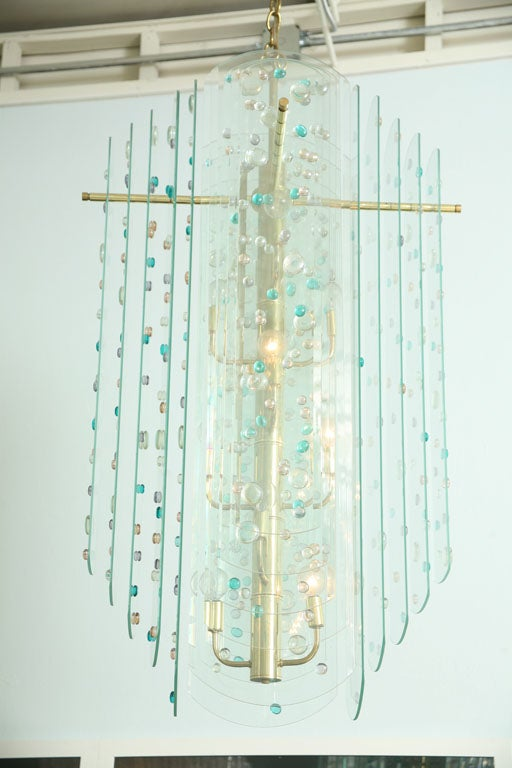 The central brass rod with staggered candle arms eminating layers of beveled glass with handblown colored discs.