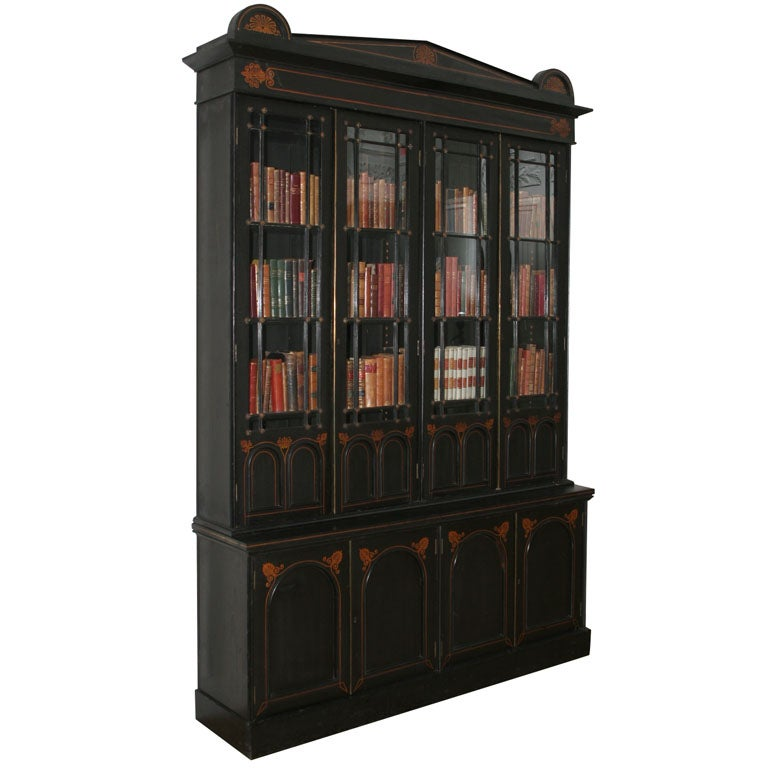 AN UNUSUAL REGENCY EBONIZED FOUR DOOR BOOKCASE