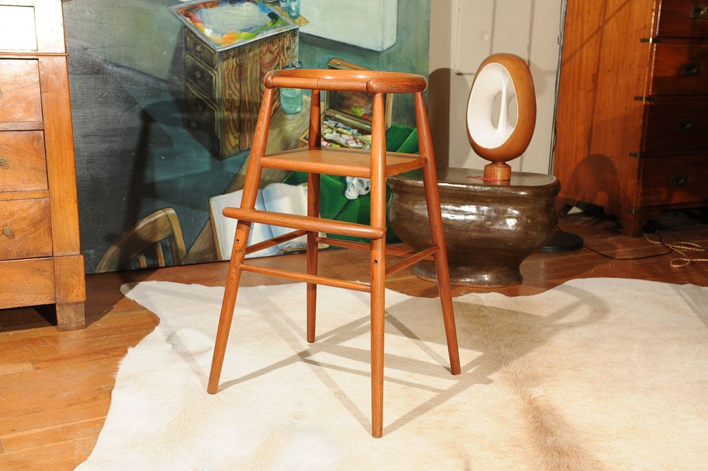 solid teak child's chair with adjustable foot rest and removable safety bar designed by Nanna Ditzel 1923-2005
