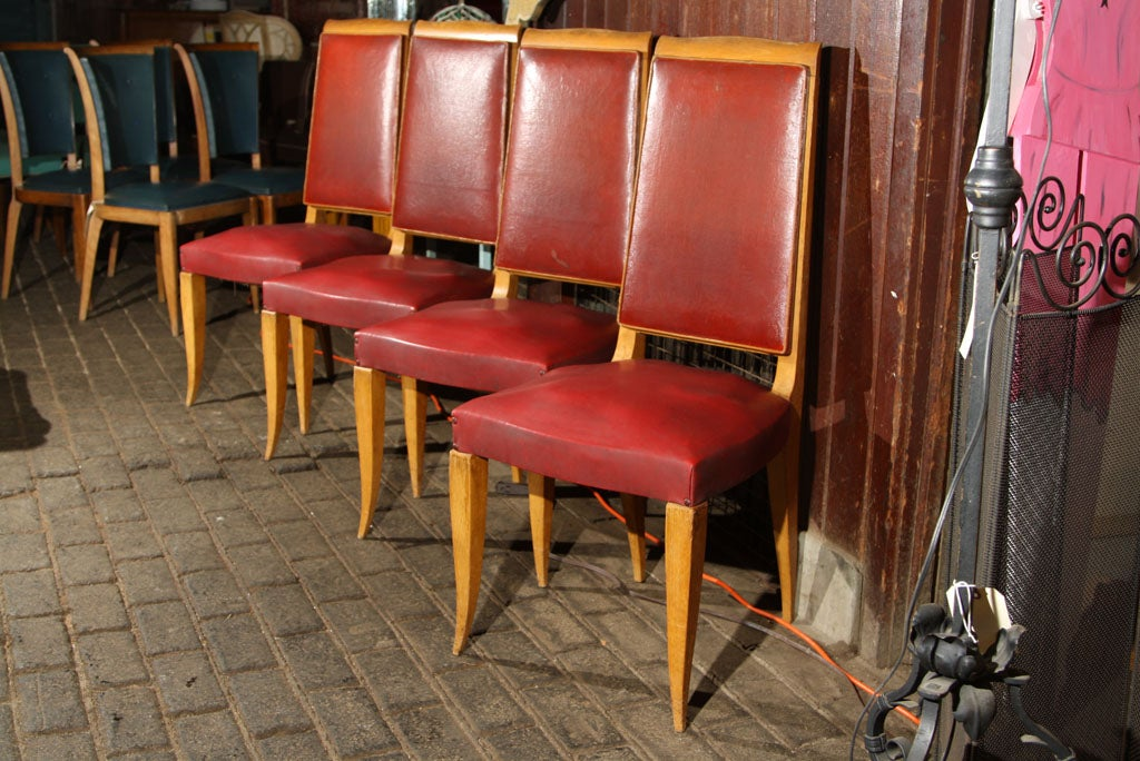 Set of four high back French dining chairs upholstered in red oil cloth with medium wood colored frames. Wood frames are sturdy. Seat springs need to be retied.