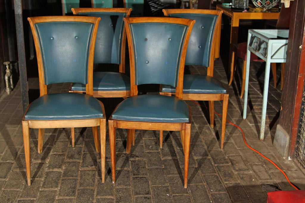 Set of four high back French dining chairs with medium wood colored frames in original blue vinyl upholstery. Frames are sturdy. Some buttons are missing.