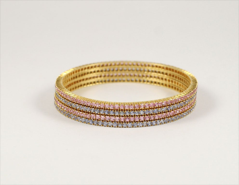 A set of Four Fabulous Pink and Blue Sapphire Bangle Bracelets, with over 80.00 Carats of Color...Set in 18 Karat Gold