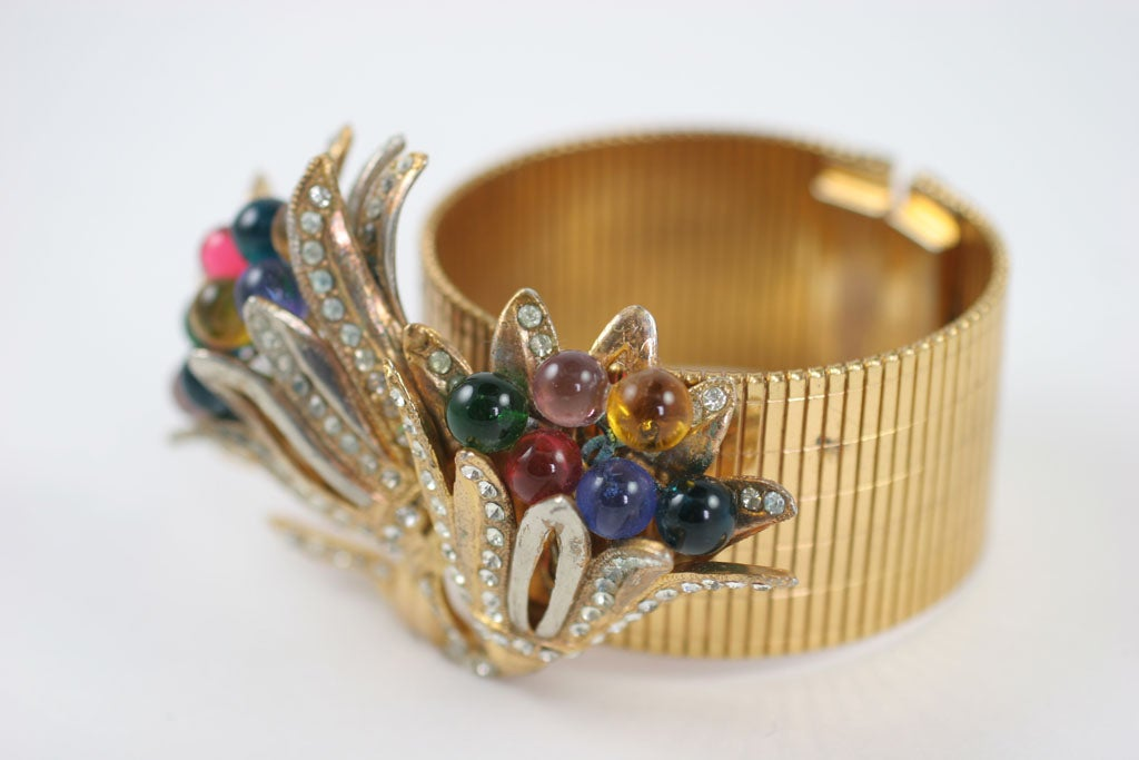Flexible wide band bracelet decorated with a large rhinestone and glass bead adorned floral cluster.