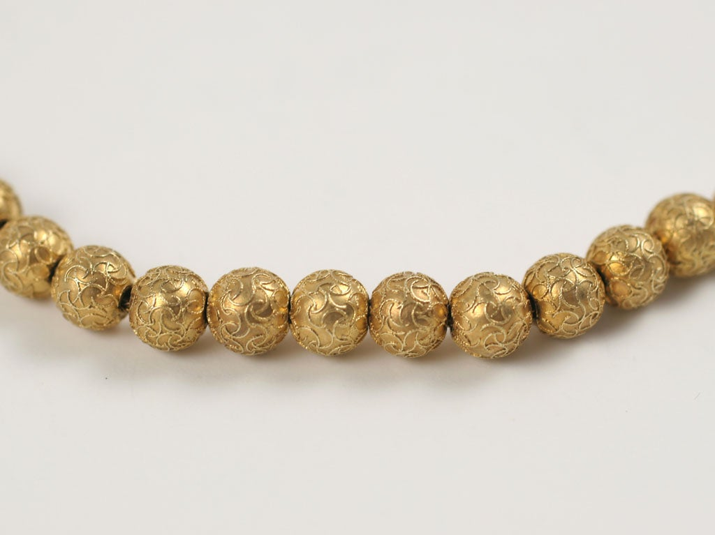 A delicate gold necklace of beads encrusted with golden strands that interweave and completely cover each bead. Without the help of a loup, the beads appear granulated as were their c.1870 etruscan revival cousins. The necklace, strung on strong
