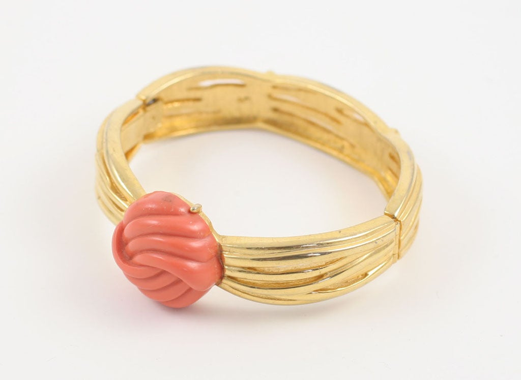 Goldtone clamp bracelet with center knot of faux coral.