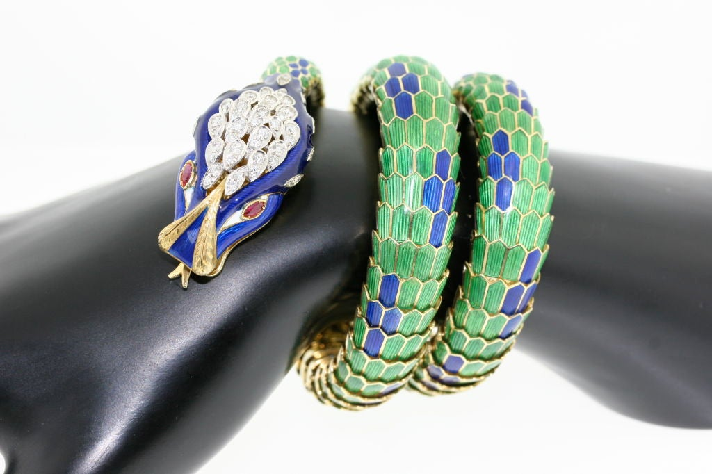 A fabulous 18k gold serpent coiled bracelet in shades of emerald green and royal blue. Impressive diamond head with ruby eyes. Nice tight coil in excellent condition. On a scale of 1 to 10 this is a 10!!