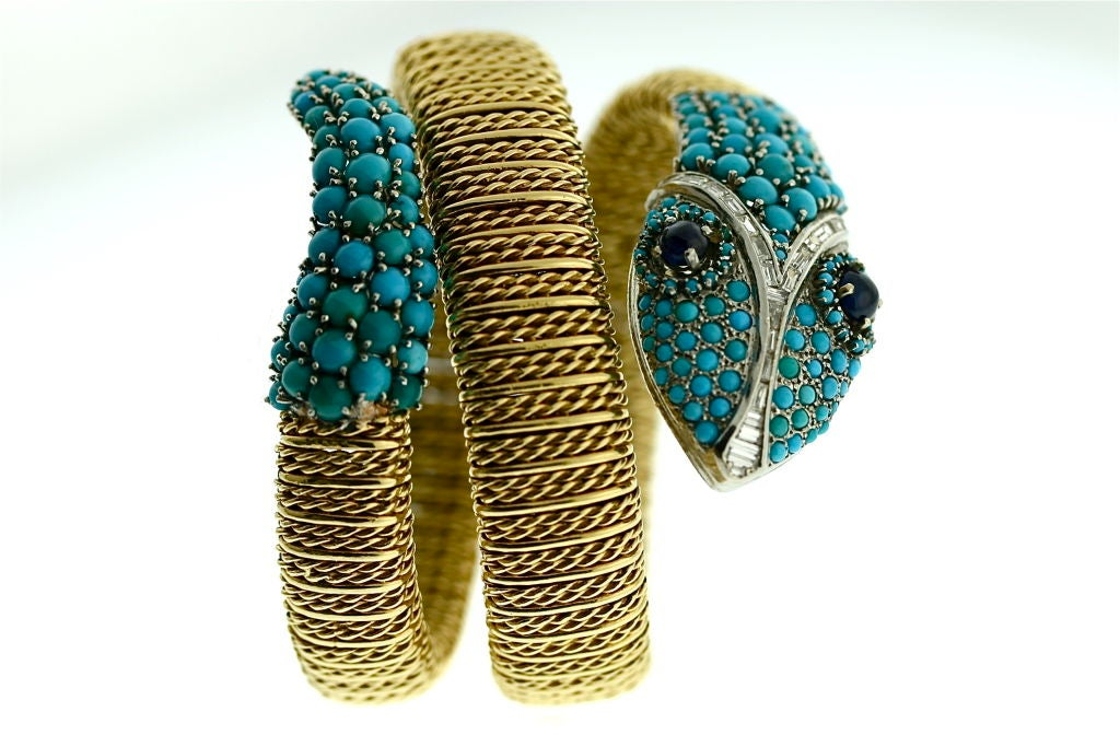 Fun and stylish 18k gold flexible serpent wrap bracelet set with turquoise stones on the tail and turquoise, diamond baguettes and cabochon sapphires on the head. A very playful and compelling bracelet. Can be worn at the wrist or higher up on the