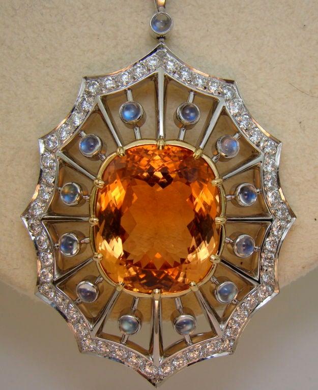 Imperial Topaz, Moonstone, & Diamond Pendant in Platinum - The pendent is designed around this fine Imperial Topaz of 25.47 carats, a beautiful reddish-orange hue. 1.15 carats of Diamonds encompass the gem with moonstones. The moonstones add their