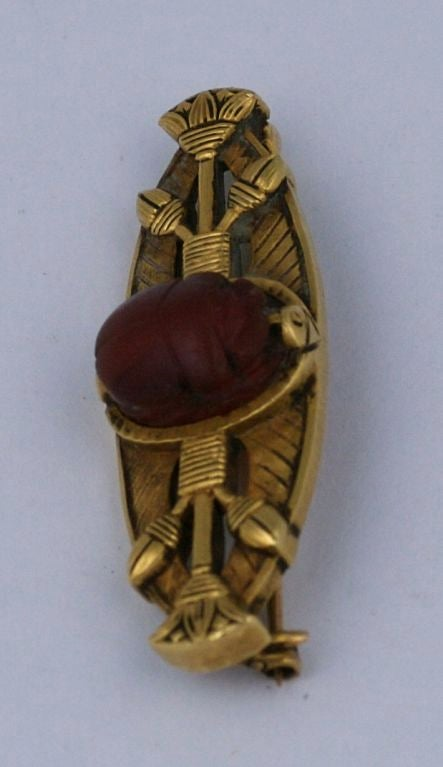 Early 20th Century brooch of heavy 18K with ancient carnelian scarab centrally mounted with lotus motifs designs. Eygptian revival motifs become popular with opening of ancient Eygptian tombs in the late 19th Century. USA 1900.  1.75