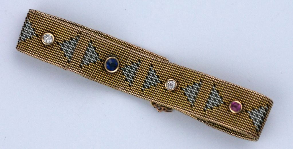 This unusual and elegant 2 tone Deco mesh band bracelet is woven with triangular motifs between bezel set stones. Realized in 14k white and yellow gold, the art deco pattern includes a patriotic mix of rubies, diamonds and a singular sapphire. <br