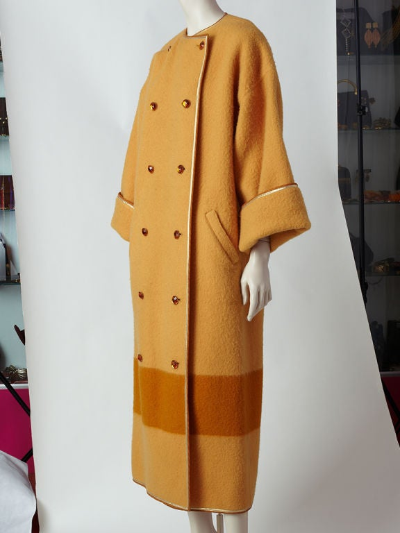 "Geoffrey Beene amber colored wool double breasted ""blanket"" coat trimmed in gold with a Kimono style cut sleeve.<br />