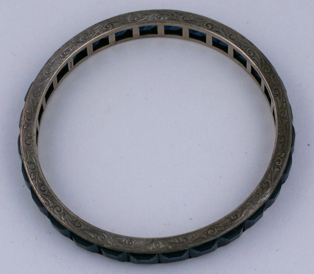 """Channel set faux sapphires give this bangle a sleek look great for stacking. This period Deco piece is set in sterling silver and has intricate hand etching around the shoulders.<br /> Excellent condition.<br /> Interior Diameter: 2.5""""<br"""