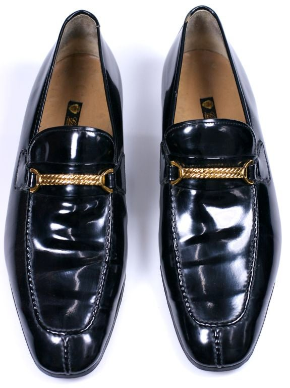 Elegant Gucci Mens Patent Loafers with twisted gilt metal decoration across instep. 1970's Italy. Excellent condition. Size 45. Measures in cm: Length 31, Widest distance on sole 10, Heel 7cm, Measure across top of shoe at widest 17.5 cm.