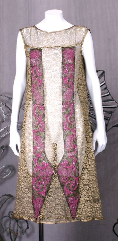 Flapper dress of floral pattern gold lame lace, beaded and embroidered with fuschia and black gold glass beads in a modified art deco swirl design. France 1920. Excellent condition, Slight loss on fuschia beading, back/right. Slip deficient.