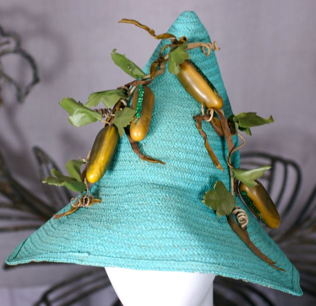 Surrealist bright turquoise straw sunhat laden with sequin trimmed composition pickles. Vines of paper tape and moss green velvet tendrils. Definitely a statement or collectors piece from the 1950s. Unusual 4 pointed brim and pointy crown.<br