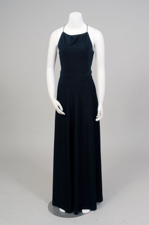 Slinky black jersey is the perfect fabric for this sexy backless dress made in England by Bernshaw.  The front of the dress has a simple and demure covered up look, with a high neckline, fitted waist and long slim skirt. When the wearer turns around