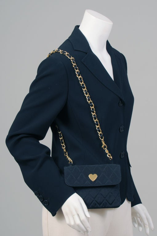 A very witty black crepe jacket from Franco Moschino incorporates a humourous replica of an iconic French shoulder bag into the design.<br /> The three button blazer style jacket in black crepe has a traditional left hip pocket with hand finishing.
