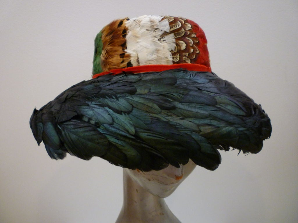 """Beautiful 1950s completely feathered hat in pheasant and coq feathers with a red velvet band from Jillé.  Inner band measures 20 1/2""""   Across brim is 12 1/2"""""""