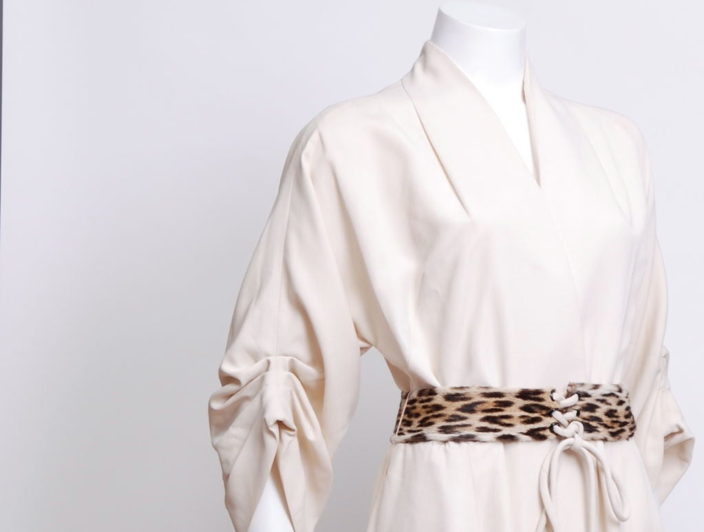Ivory faille long wrap hostess gown, sleeves have four tucked pleat, leopard fur front lacing belt. This gown is deadstock (never worn with original tag attached).