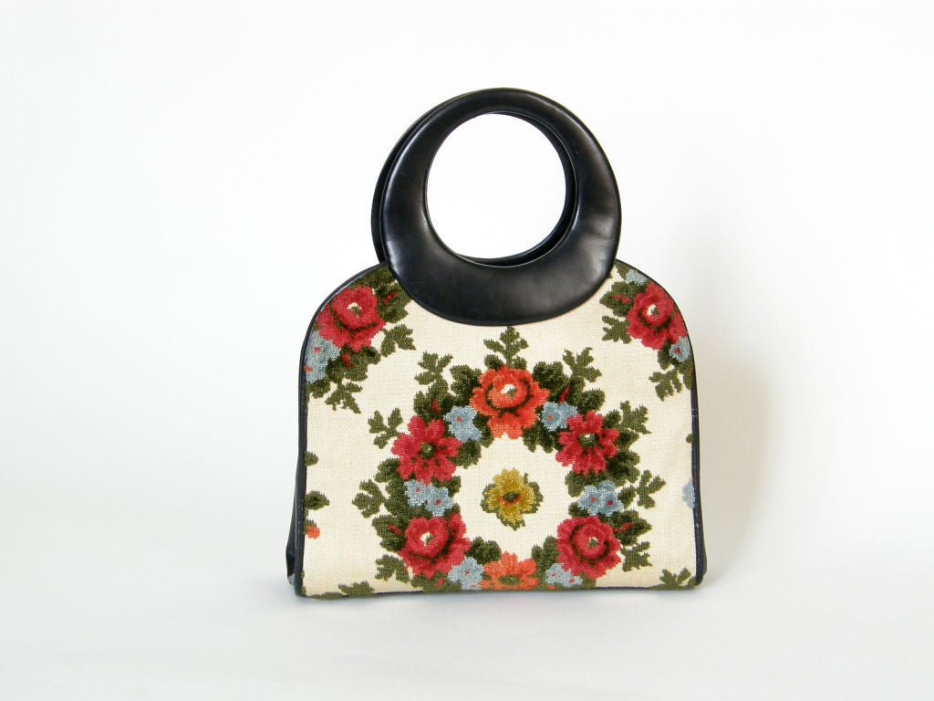 This lovely c. 1950s or 1960s Holzman handbag has front and back panels made from a tapestry fabric with raised floral patterns. The side panels and bottom are black leather. The black satin lined interior compartment has two slip pockets, one