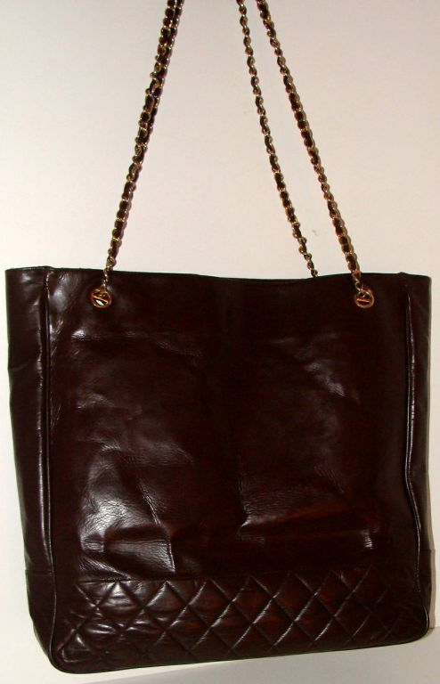 Large dark brown tote with quilting near the base. Woven chain shoulder straps with pads. Leather fob with Chanel logo hangs from one shoulder strap. You may already have a Chanel bag in black, but do you have one in this rich deep brown?  This tote