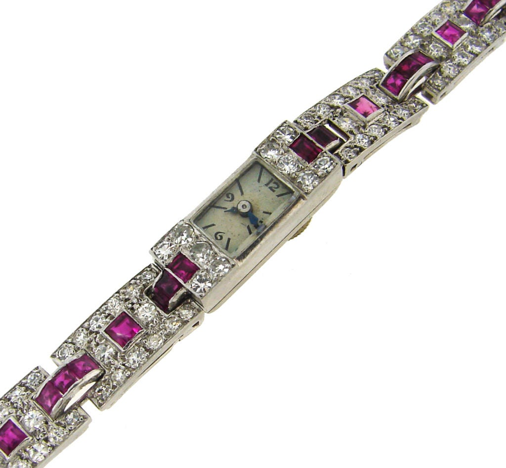 Elegant and delicate Art Deco watch created by Cartier in the  1930's. It is platinum and tastefully set with the finest quality diamonds and rubies. The workmanship is outstanding. The watch has a white face and dark blue hands and a hidden