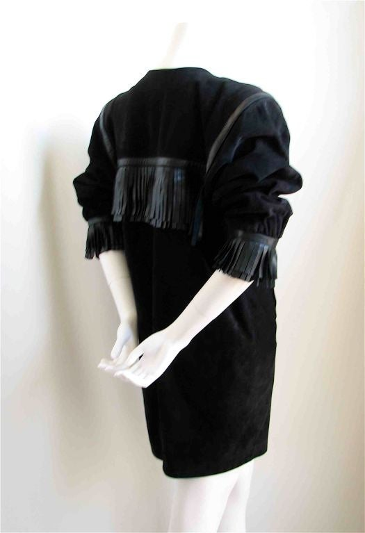 Unique suede dress with leather fringed detail from Yves Saint Laurent rive gauche dating to 1987. Very strong silhouette with padded shoulders. Buttons up front with three buttons. Jet black in color. Fully lined. Pockets at hips. Fr 40. Best for a