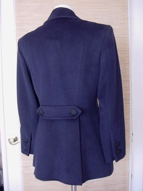 Ines de la Fressange rich navy lush warm cashmere blend. 4 on 2 Double breasted jacket with 2 sculpted flap pockets.   The actual pockets are on interior, the flaps are sculpted with a button. The rear has a double centered vent created by a 'flap'