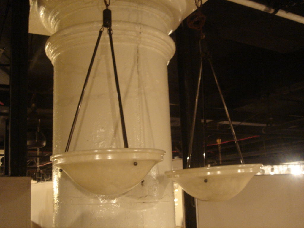 Pair of vintage Alabaster hanging light fixtures. France, circa 1940. Priced individually; two available.  Features polished alabaster shades in bone white with patinated (blackened) brass metal hanging poles.  Dimensons: Each alabaster shade