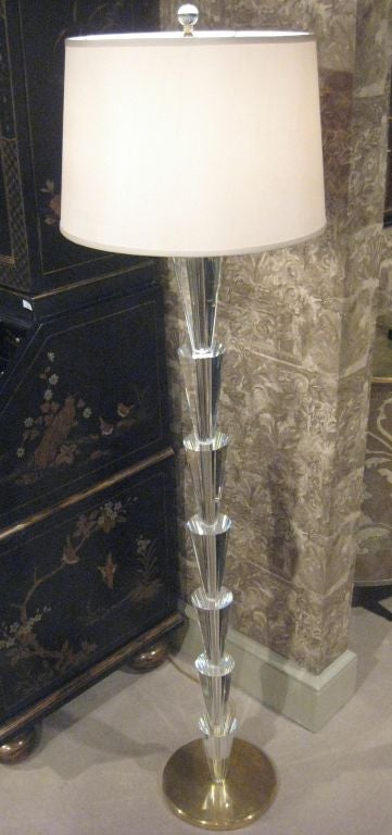 Two sober and elegant Italian Mid-Century style solid crystal standing lamps in the Modern Neoclassical spirit with each piece of crystal delicately cut to reflect light, tapered and arranged sequentially on top of each other and resting on brass