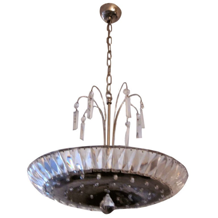 An elegant French midcentury crystal chandelier/fixture embracing neoclassicism and modernity.  The piece has a silvered nickel metal center plate that is im-bedded with cut crystal and central hanging ball. Sockets are secluded above the central