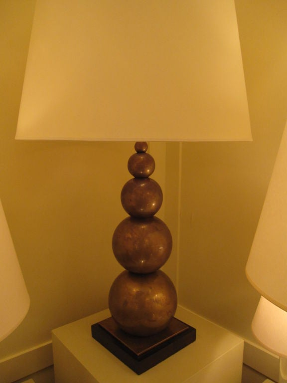 "Two elegant pairs of solid brass table lamps consisting of four stacked balls upon a sober base (base: 7.25""). A ball finial completes the lamps.