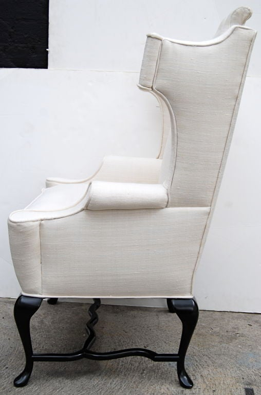 A really fun Arturo Pani wing chair. Restored in a Van Dyke finish on the legs and upholstered in an off-white tussah silk. 