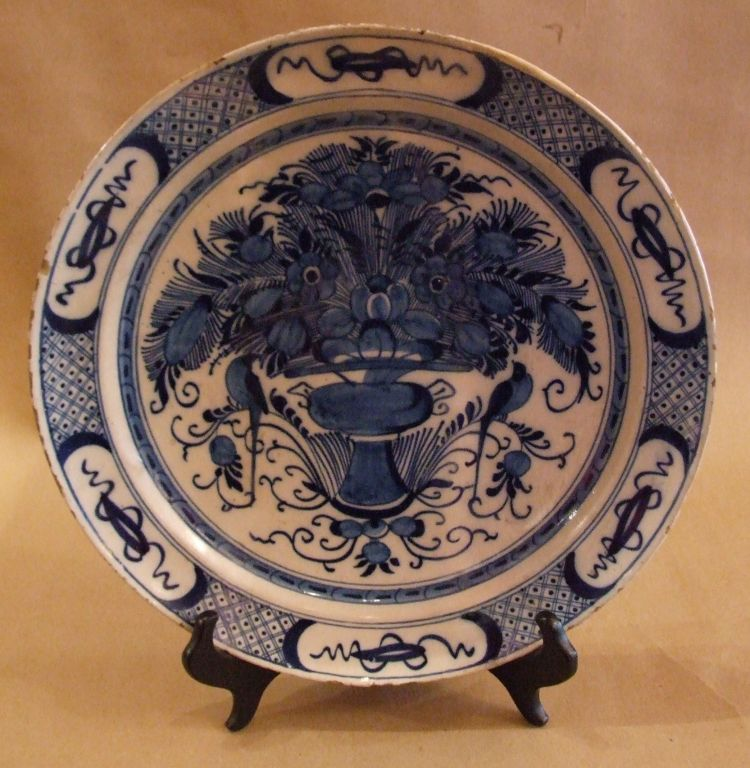 18th Century Dutch delft charger in blue and white having a diaper and squiggle lozenge border, the center with flowering urn surmounted with a pair of lovebirds perched on branches.
